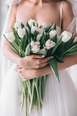 Wedding bouquet of white tulips in the hands of a beautiful bride indoor. Selective Focus