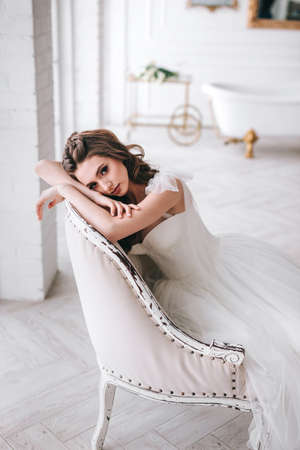 Beautiful young bride posing in home on wedding day Standard-Bild