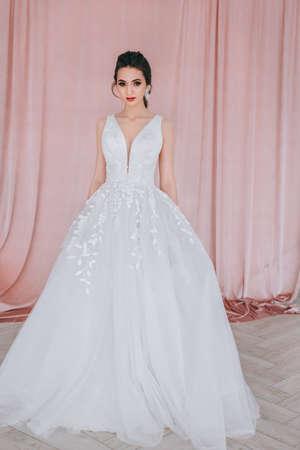 Charming and beautiful bride in luxury fashion wedding dress in studio Standard-Bild