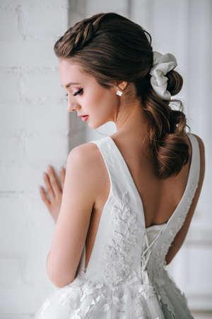 Back view of the elegant blonde bride dressed in a white dress in studio Standard-Bild