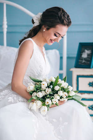 Beautiful bride with a wedding bouquet sitting on bed indoors in studio interior like at home.