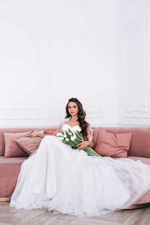 Bride in beautiful dress holding wedding bouquet and sitting on sofa indoors