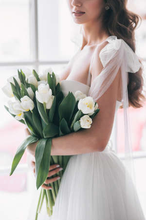 Wedding bouquet of white tulips in the hands of a beautiful bride. Soft Focus
