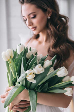 Wedding bouquet of white tulips in the hands of a beautiful bride indoor. Selective soft Focus