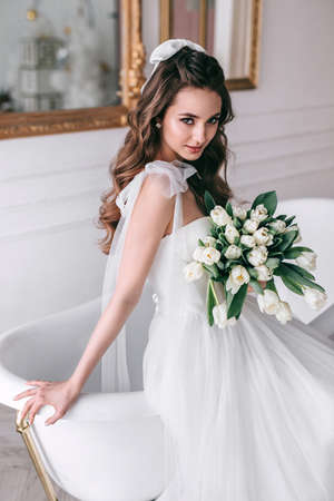 Young bride in wedding dress holding bouquet of white tulips in studio Standard-Bild