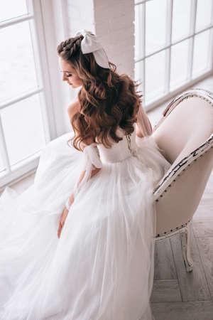 Fashion photo of beautiful bride with dark hair in luxurious wedding dress