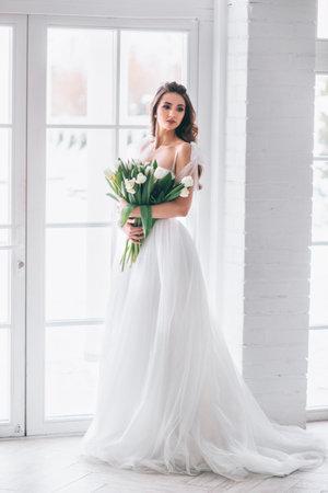 Beautiful brunette woman as bride with wedding bouquet in studio