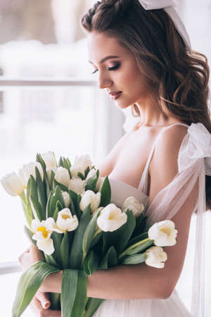 Wedding bouquet of white tulips in the hands of a beautiful bride. Selective Focus