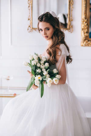 Portrait of a beautiful bride with a bouquet in studio