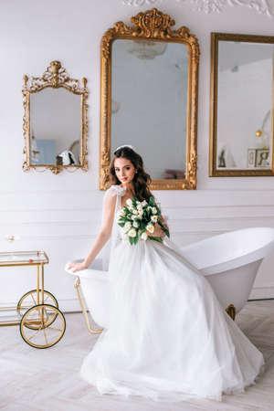 Beautiful brunette bride posing in white dress with wedding bouquet in studio Фото со стока