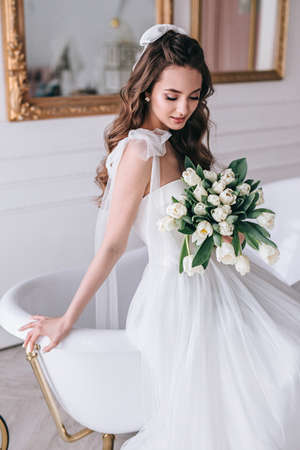 Beautiful bride with a wedding bouquet sitting on sofa indoors in white studio interior like at home.