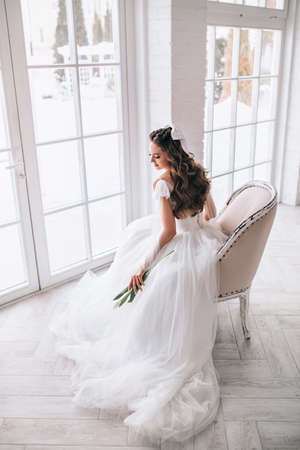 Bride woman in a wedding dress sitting at the window and waiting for the wedding ceremony
