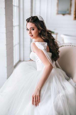 Fashion photo of beautiful bride with dark hair in luxurious wedding dress in studio