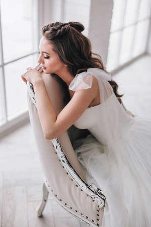 Beautiful romantic bride in wedding dress sitting in studio Фото со стока
