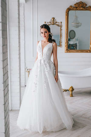 Charming and beautiful bride in luxury fashion wedding dress in studio Фото со стока
