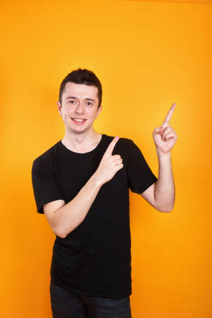 Portrait of an excited man in black clothes showing thumbs up on yellow background Фото со стока