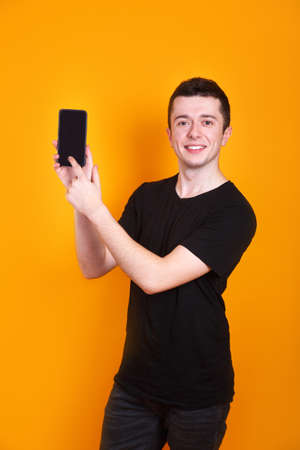 Smilibg young man in black t-shirt presenting smart phone on yellow background