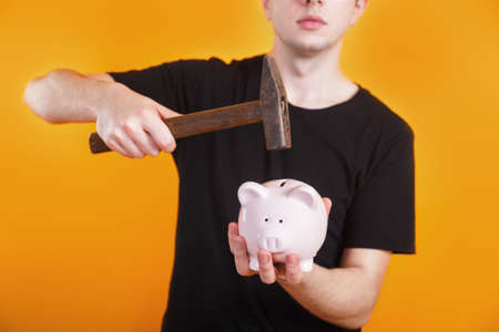 Man holds a hammer that is raised above a piggy bank with money to break it.