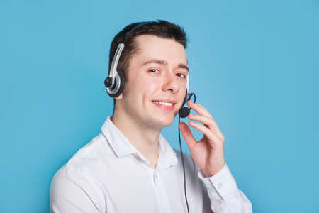 Smiling call center operator on blue background. Headset touching. Фото со стока