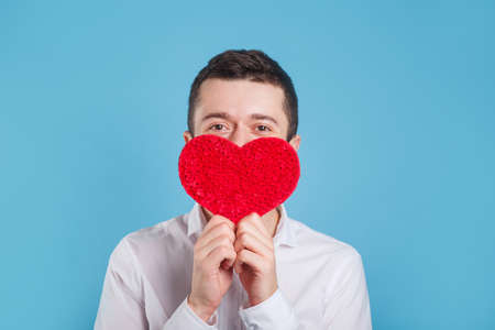 Young man in white shirt holding red love heart over eyes on blue background