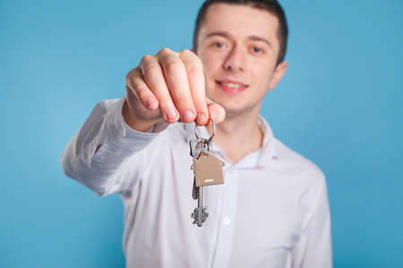 Agent businessman with keys . Holding out house keys on a house shaped keychain