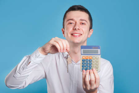 Agent businessman with house keys and calculator on blue background Фото со стока