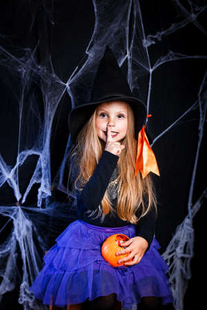 Little girl in witch Halloween costume having fun . Trick or treat Фото со стока