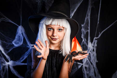 Little girl in witch Halloween costume having fun . Little witch