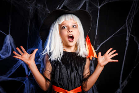 Little girl in witch costume having fun on Halloween trick or treat