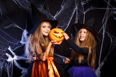 Two little kids in witch costumes having fun on Halloween