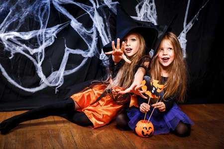Two little girls in witch costumes having fun on Halloween . Trick or treat