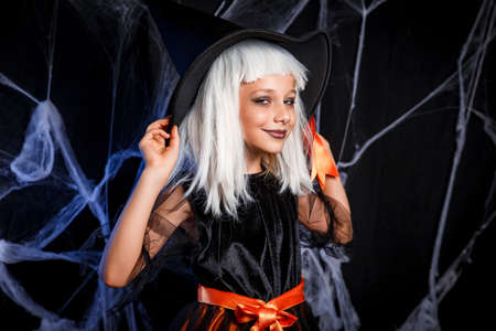 Little girl in witch Halloween costume with white hair having fun . Little witch