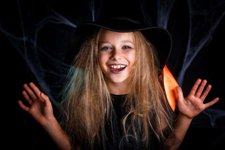 Little girl in witch costume having fun on Halloween trick or treat.