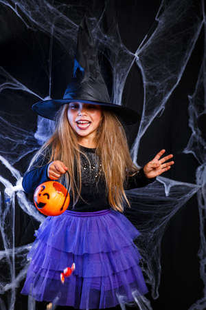Cute happy little girl dressed up as witch with bucket of candy on Halloween background