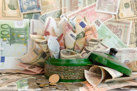 bringing: A lot of money in green money box. Various World Currencies