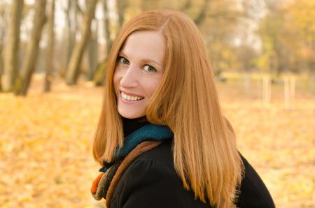 dientes sanos: Retrato al aire libre de la muchacha pelirroja con ojos verdes. Color del otoño Foto de archivo