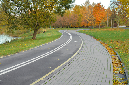 wheeling: Parallel bicycle and pedestrian road in autumn park