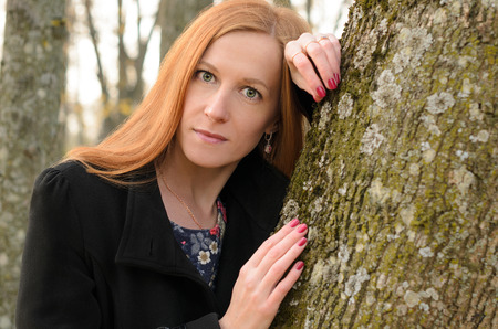 ojos verdes: Outdoor portrait of red haired woman with green eyes. A young woman stands near tree