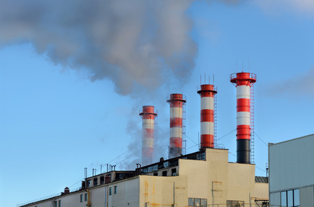 emissions: Four striped industrial chimneys. Plant emissions