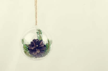 clear day in winter time: Transparent Christmas ball with a pine cone inside Stock Photo
