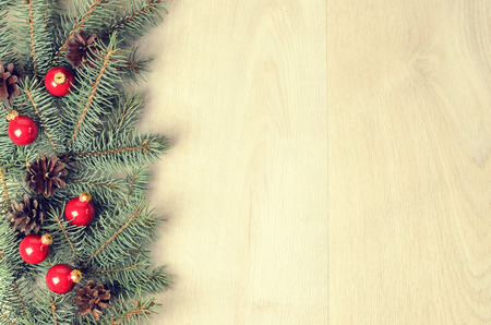 branch of a christmas tree: branches of blue spruce, red balls and fir cones on a  wooden background