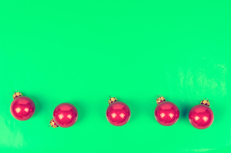 stuffer: Five Christmas balls crimson color on a contrasting green background