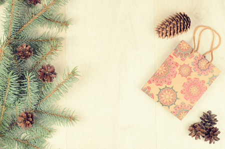 stuffer: branches of blue spruce, cones and paper shopping gift bag on a wooden background. christmas background