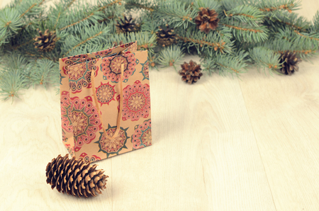 branches of blue spruce, cones and paper shopping gift bag on a wooden background. christmas background