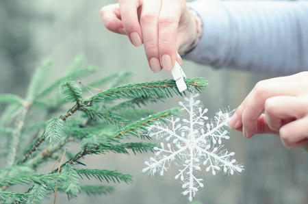 Woman hand creating christmas decoration outdoor. Winter forest