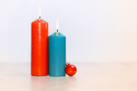 1 2 month: Two candles and a Christmas ball on a wooden  surface