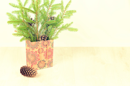 stuffer: branches of fir, cones and paper shopping gift bag on a wooden background. christmas background