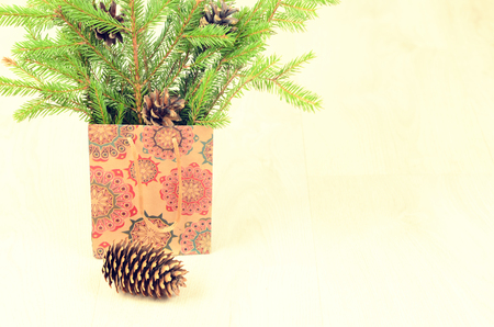 branches of fir, cones and paper shopping gift bag on a wooden background. christmas background