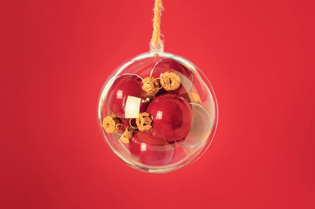 clear day in winter time: Transparent ball with a red christmas balls inside on red background