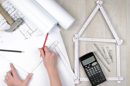 building sector: Hands of engineer working with the tool on project drawings background